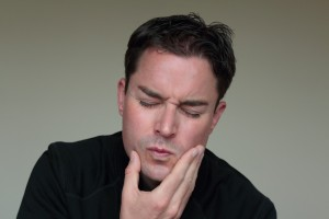 Man with toothache holding his face in pain