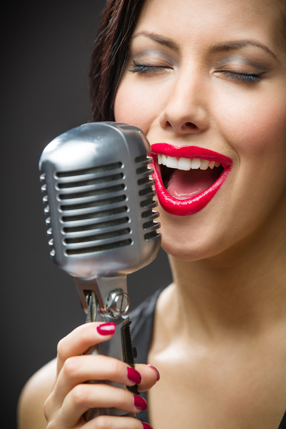 Headshot of female singer with closed eyes keeping microphone on grey background. Concept of music and retro fashion