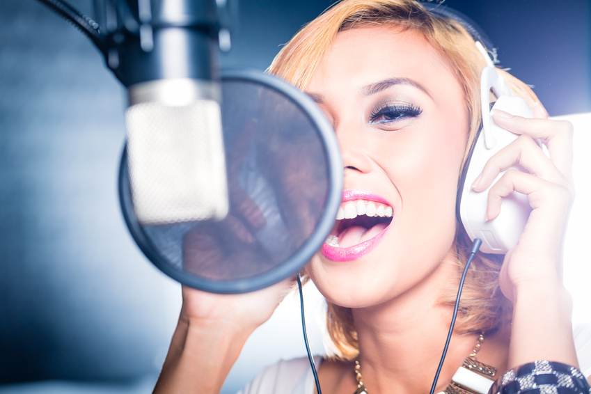 Asian singer producing song in recording studio