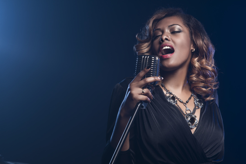 Beautiful African woman singing with the microphone